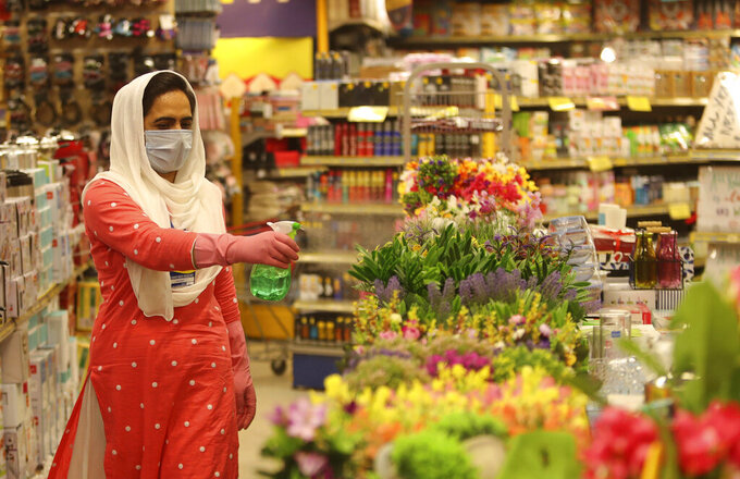 A worker sanitizes products in a shop at a mall in Jammu, India, Thursday, June 11, 2020. Two and a half months of nationwide lockdown kept numbers of infections relatively low in India. But with restrictions easing in recent weeks, cases have shot up with India's tally becoming the fifth highest in the world, raising questions about whether authorities have done enough to avert catastrophe. (AP Photo/Channi Anand)