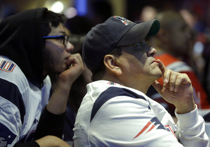 New England Patriots fan Victor Polanco, right, watches the second half of the NFL Super Bowl 53 football game in Atlanta between the New England Patriots and the Los Angeles Rams at a bar in Boston Sunday, Feb. 3, 2019. (AP Photo/Steven Senne)
