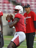 FILE - In this  Saturday, Aug. 11, 2018 file photo, with his coaches looking on, Louisville quarterback Jawon Pass attempts a pass during Louisville Football Fan Day in Louisville, Ky. Pass will be the starter for Louisville, replacing Heisman Trophy winner Lamar Jackson. (AP Photo/Timothy D. Easley, File)