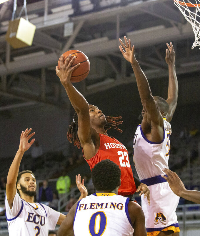 Houston's Cedrick Alley Jr., center, attempts a shot over East Carolina's Justice Obasohan, right, Isaac Fleming (0), and K.J. Davis (2) during the second half of an NCAA college basketball game in Greenville, N.C., Wednesday, Feb. 27, 2019. (AP Photo/Ben McKeown)