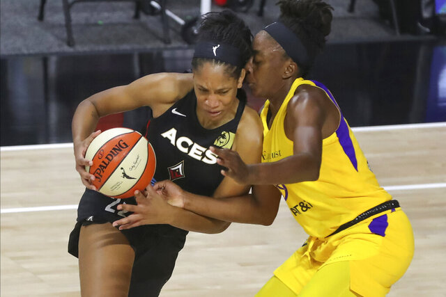 Las Vegas Aces' A'ja Wilson, left, drives against Los Angeles Sparks' Nneka Ogwumike during the first half of a WNBA basketball game Saturday, Sept. 12, 2020, in Bradenton, Fla. (AP Photo/Mike Carlson)