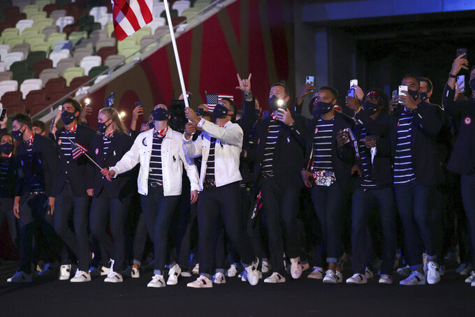 Sue Bird and Eddy Alvares, of the United States, carry their country's flag during the opening ceremony in the Olympic Stadium at the 2020 Summer Olympics, Friday, July 23, 2021, in Tokyo, Japan. (Hannah McKay/Pool Photo via AP)