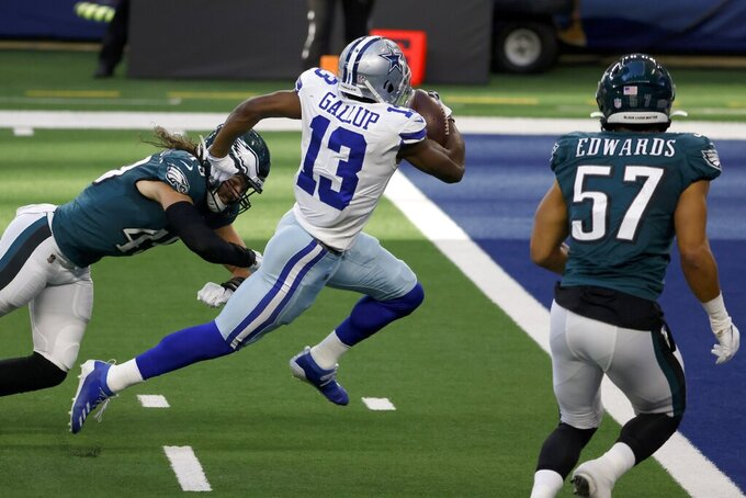 Philadelphia Eagles linebacker Alex Singleton, left, and T.J. Edwards (57) are unable to stop Dallas Cowboys wide receiver Michael Gallup (13) from reaching the end zone for a touchdown after catching a pass in the first half of an NFL football game in Arlington, Texas, Sunday, Dec. 27. 2020. (AP Photo/Ron Jenkins)