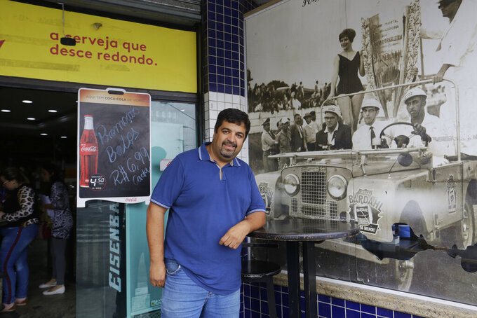 In this Nov. 7, 2019 photo, Marcos Resenti, owner of a bakery located next to the Interlagos racetrack, poses for a photo in front of an old photo showing a race at Interlagos, in Sao Paulo, Brazil. Resenti said he was was shocked when he heard President Jair Bolsonaro announced in June there was a 99% chance F1 would move to Rio de Janeiro. (AP Photo/Nelson Antoine)