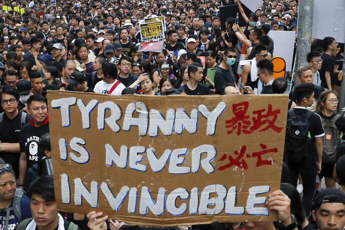 Tens of thousands of protesters carry posters and banners march through the streets as they continue to protest an extradition bill, Sunday, June 16, 2019, in Hong Kong. Hong Kong residents were gathering Sunday for another mass protest over an unpopular extradition bill that has highlighted the territory's apprehension about relations with mainland China. (AP Photo/Kin Cheung)