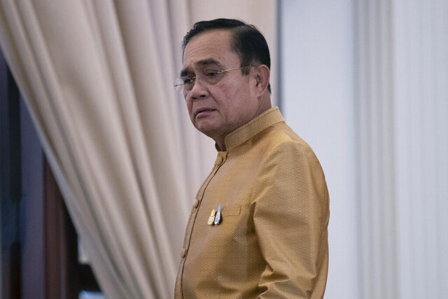 Thailand's Prime Minister Prayuth Chan-ocha leaves after a press conference at Government House in Bangkok, Thailand, Tuesday, Dec. 1, 2020. Thailand's highest court Wednesday acquitted Prayuth of breaching ethics clauses in the country's constitution, allowing him to stay in his job. (AP Photo/Sakchai Lalit)