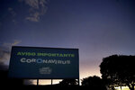 A sign that flashes different warnings about coronavirus, in Portuguese, stands tall at a drive-in movie theater where drivers must leave one space empty between them in Brasilia, Brazil, Saturday, May 23, 2020. The drive-in was closed at the start of the pandemic but reopened to the public at the start of April. (AP Photo/Eraldo Peres)
