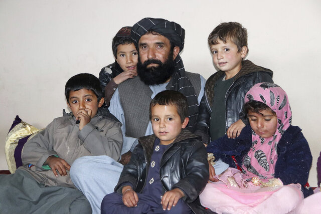 Abdul Manan, a 58-year-old tribal leader, poses with his children after an interview in southern Uruzgan province of Afghanistan, Saturday, Nov. 14, 2020. An Afghan rights watchdog and a tribal leader are cautiously welcoming an expected Australian government report into suspected war crimes by its special forces in Afghanistan following a four-year investigation. (AP Photo/Shareefullah Sharafat)