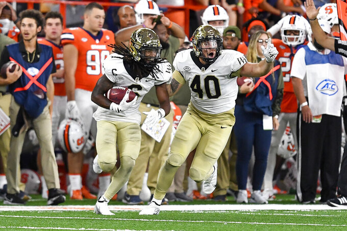 Wake Forest defensive back Ja'Sir Taylor, left, celebrates with defensive lineman Rondell Bothroyd (40) after recovering a fumble by Syracuse running back Cooper Lutz during the second half of an NCAA college football game in Syracuse, N.Y., Saturday, Oct. 9, 2021. (AP Photo/Adrian Kraus)