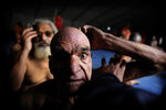 In this Jan. 27, 2019, photo, Hindu men get their hair cut in a ritual before becoming Naga Sadhus or naked holy men at Sangam, the confluence of three holy rivers during the Kumbh Mela or pitcher festival in Prayagraj Uttar Pradesh state, India. At every Kumbh, including this year's, thousands of devotees were initiated into the reclusive sect of the Naga Sadhus, naked, ash-smeared cannabis-smoking Hindu warriors and onetime-armed defenders of the faith who for centuries have lived as ascetics in jungles and caves. (AP Photo/Rajesh Kumar Singh)