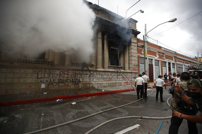 Clouds of smoke shoot out from the Congress building after protesters set a part of the building on fire, in Guatemala City, Saturday, Nov. 21, 2020. Hundreds of protesters were protesting in various parts of the country Saturday against Guatemalan President Alejandro Giammattei and members of Congress for the approval of the 2021 budget that reduced funds for education, health and the fight for human rights. (AP Photo/Moises Castillo)