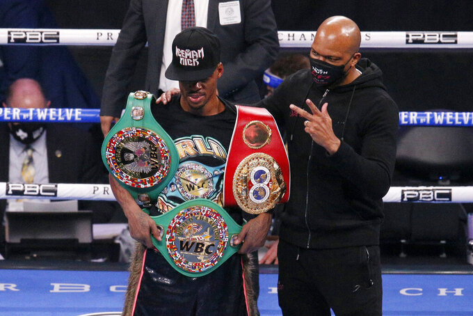 Errol Spence Jr., poses by trainer Derrick James after defeating Danny Garcia for the WBC IBF welterweight championships in a boxing bout in Arlington, Texas, Saturday, Dec. 5, 2020. (AP Photo/Brandon Wade)