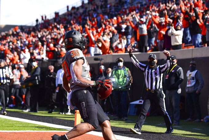 Oklahoma State fans cheer as running back Chuba Hubbard (30) scores a touchdown against Iowa State during the first half of an NCAA college football game Saturday, Oct. 24, 2020, in Stillwater, Okla. (AP Photo/Brody Schmidt)