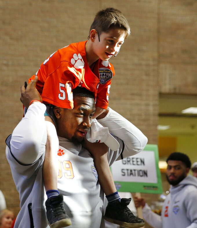 Clemson Tigers defensive end Clelin Ferrell (99) holds Layton Horner on his shoulders as they enter the main area during a hospital visit at Texas Scottish Rite Hospital in Dallas on Thursday, Dec. 27, 2018. The Clemson Tigers will play the Notre Dame Fighting Irish in the Cotton Bowl this coming Saturday at AT&T Stadium in Arlington, Texas. (Vernon Bryant/The Dallas Morning News via AP)