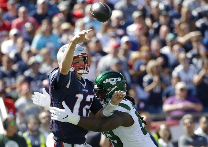New England Patriots quarterback Tom Brady (12) passes under pressure from New York Jets nose tackle Steve McLendon (99) in the first half of an NFL football game, Sunday, Sept. 22, 2019, in Foxborough, Mass. (AP Photo/Elise Amendola)