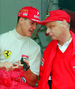 FILE - In this Thursday May 16, 1996 file photo defending champion Michael Schumacher of Germany, left, chats with Ferrari consultant Niki Lauda during the practice session for the Monaco F1 Grand Prix in the principality. Three-time Formula One world champion Niki Lauda, who won two of his titles after a horrific crash that left him with serious burns and went on to become a prominent figure in the aviation industry, has died. He was 70. (AP Photo/Lionel Cironneau, File)