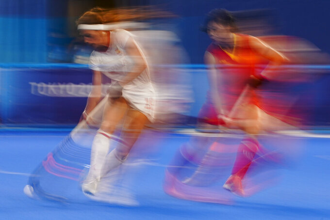 Spain's Begona Garcia Grau, left, drives the ball past China's Jinrong Zhang, right, during a women's field hockey match at the 2020 Summer Olympics, Thursday, July 29, 2021, in Tokyo, Japan. (AP Photo/John Minchillo)