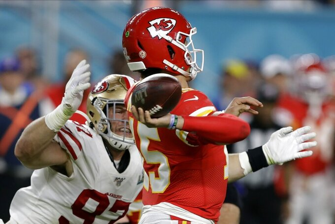 Kansas City Chiefs quarterback Patrick Mahomes passes under pressure from San Francisco 49ers' Nick Bosa, left, during the first half of the NFL Super Bowl 54 football game Sunday, Feb. 2, 2020, in Miami Gardens, Fla. (AP Photo/Chris O'Meara)