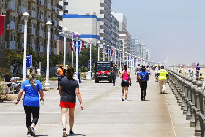 Board walks visitors keep their social distance on the oceanfront Friday, May 22, 2020, in Virginia Beach, Va. Virginia Gov. Ralph Northam lifted restrictions and opened the beachfront beginning Friday. (AP Photo/Steve Helber)