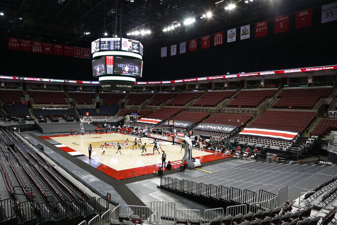FILE-  In this Sunday, Dec. 13, 2020, file photo, Cleveland State plays against Ohio State during the first half of an NCAA college basketball game with no fans in the stands at Value City Arena in Columbus, Ohio. This pandemic-altered season has turned into quite the isolation play. With campuses largely empty and arena doors closed to fans in many places, the games have more than ever been reduced to television programming. (AP Photo/Jay LaPrete, File)
