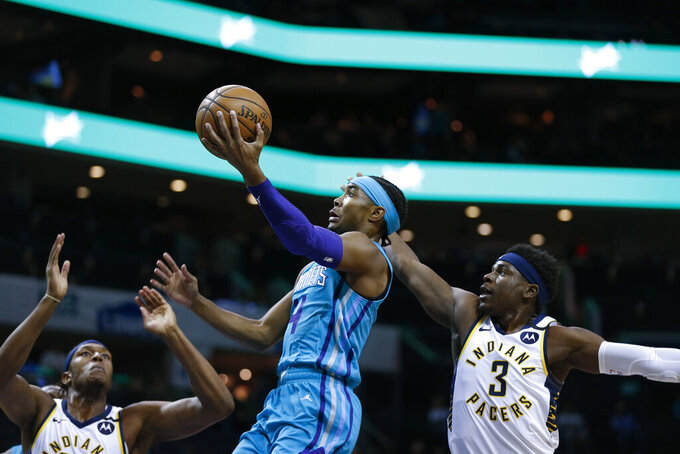 Charlotte Hornets guard Devonte' Graham, center, drives to the basket between Indiana Pacers center Myles Turner, left, and guard Aaron Holiday in the first half of an NBA basketball game in Charlotte, N.C., Monday, Jan. 6, 2020. (AP Photo/Nell Redmond)