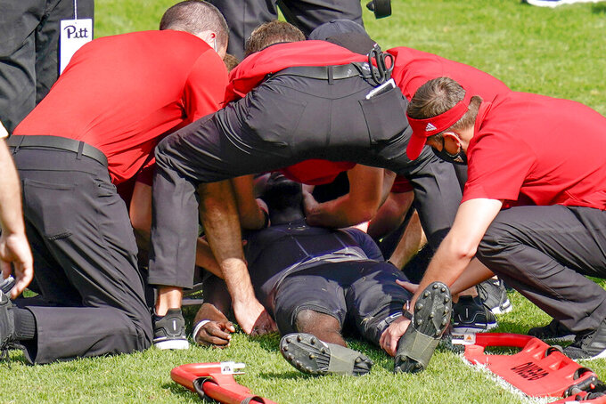 Trainers tend to Louisville quarterback Malik Cunningham (3) after he was injured during the second half of an NCAA college football game against Pittsburgh, Saturday, Sept. 26, 2020, in Pittsburgh. (AP Photo/Keith Srakocic)