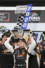 Noah Gragson holds up the trophy after winning the NASCAR Xfinity series auto race at Daytona International Speedway, Saturday, Feb. 15, 2020, in Daytona Beach, Fla. (AP Photo/Terry Renna)