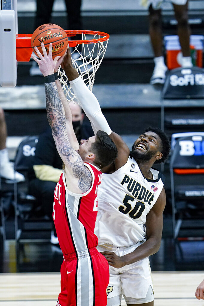 Purdue forward Trevion Williams (50) blocks the shot over Ohio State forward Kyle Young (25) in the first half of an NCAA college basketball game at the Big Ten Conference tournament in Indianapolis, Friday, March 12, 2021. (AP Photo/Michael Conroy)