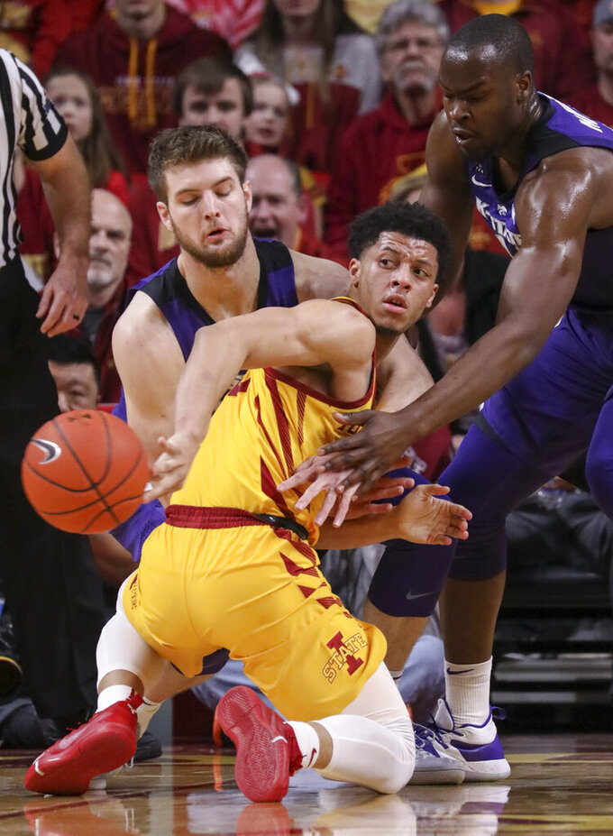 Iowa State guard Lindell Wigginton tosses a behind the back pass after losing his balance and falling down as he was defended by Kansas State forward Dean Wade and Kansas State forward Makol Mawien during the second half of an NCAA college basketball game, Saturday, Jan. 12, 2019, in Ames, Iowa. Kansas State won 58-57. (AP Photo/Justin Hayworth)