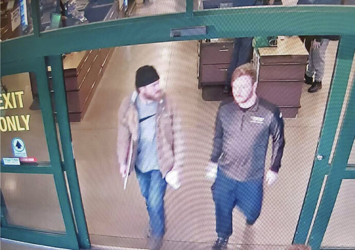 "This image from a Jan. 1, 2020 surveillance video and released in a U.S. Attorney detention memorandum, shows Brian Mark Lemley Jr, right, and Patrik Mathews leaving a store in Delaware where they purchased ammunition and paper shooting targets. The pair, along with William Garfield Bilbrough IV,  plotted to carry out ""essentially a paramilitary strike"" at a Virginia gun rights rally, a federal prosecutor said Wednesday, Jan. 22, 2020. FBI agents arrested Mathews, Lemley and Bilbrough on Jan., 16, as part of a broader investigation of The Base, a white supremacist group.  (U.S. Attorney via AP)"
