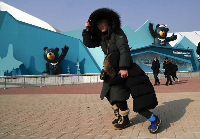 A woman shields her face and a child from gusty winds that whipped through Gangneung Olympic Park at the 2018 Winter Olympics in Gangneung, South Korea, Wednesday, Feb. 14, 2018. Spectators were advised to either stay inside venues or leave the park because of high winds. (AP Photo/Julie Jacobson)