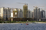This July 6, 2019 photo shows residential towers in District 22, that consists of apartment high-rises and shopping malls arranged around an artificial lake called Chitgar, under construction on the northwestern edge of Tehran, Iran. Iran's large middle class has been hit hard by the fallout from unprecedented U.S. sanctions, including the collapse of the national currency. Perhaps most devastating has been the doubling of housing prices. The spike has uprooted tenants and made home ownership unattainable for most. (AP Photo/Ebrahim Noroozi)