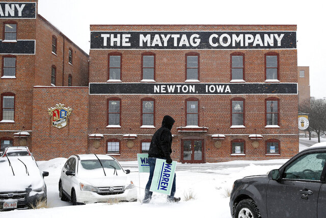 Volunteer Erick Zehr carries campaign signs outside a venue as snow falls before an event with Democratic presidential candidate Sen. Elizabeth Warren, D-Mass., Friday, Jan. 17, 2020, in Newton, Iowa. (AP Photo/Patrick Semansky)