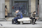 People wearing face masks sits on a bench in Milan, Italy, Thursday, Feb. 27, 2020. In Europe, an expanding cluster in northern Italy is eyed as a source for transmissions. (AP Photo/Luca Bruno)