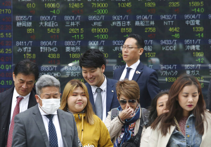 People stand in front of an electronic stock board of a securities firm in Tokyo, Wednesday, April 17, 2019. Shares were mixed in a narrow range Wednesday as China announced its economy grew at a 6.4 percent annual pace in the last quarter. (AP Photo/Koji Sasahara)