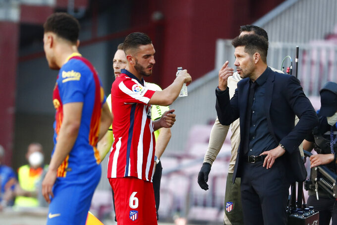 Atletico Madrid's head coach Diego Simeone, right, speaks with his player Koke during a water break during the Spanish La Liga soccer match between FC Barcelona and Atletico Madrid at the Camp Nou stadium in Barcelona, Spain, Saturday, May 8, 2021. (AP Photo/Joan Monfort)