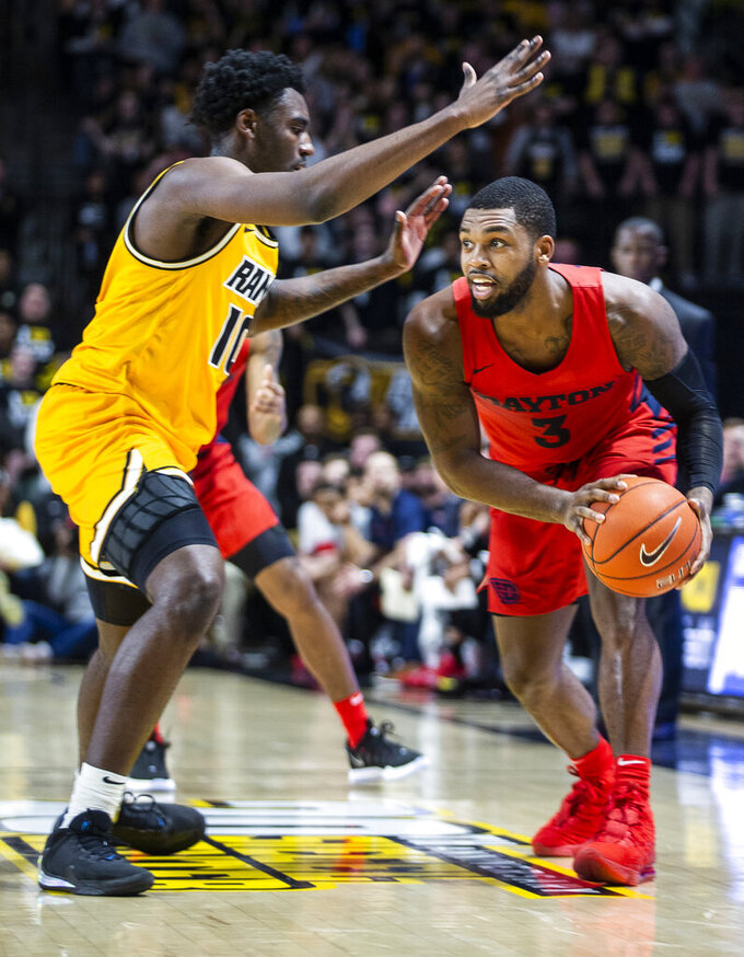 VCU guard Vince Williams (10) plays defense against Dayton guard Trey Landers (3) during the first half of an NCAA college basketball game, Tuesday, Feb. 18, 2020, in Richmond, Va. (AP Photo/Zach Gibson)