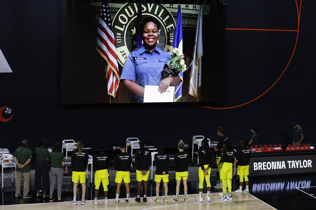 FILE - In this July 30, 2020, file photo members of the Seattle Storm stand in front of a photo of Breonna Taylor before a WNBA basketball game against the Washington Mystics in Bradenton, Fla. Taylor was killed in her home by police officers. Americans' suggestions of suitable statuesfor President Donald Trump's planned National Garden of American Heroes are in, and they look considerably different from the predominantly white worthies that the administration has locked in for many of the pedestals. Lehigh County, Pennsylvania Commissioner Amy Zanelli, suggested George Floyd, Breonna Taylor, and other Black Americans whose killings by police sparked massive street protests. (AP Photo/Chris O'Meara, File)