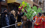Participants with a dragon caricature mingle with revelers during the Lunar New Year parade in the Chinatown neighborhood of New York, Sunday, Feb. 9, 2020. (AP Photo/Craig Ruttle)