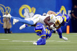 Los Angeles Chargers wide receiver Josh Palmer (5) is tackled by Los Angeles Rams defensive back JuJu Hughes (23) and another defender during the first half of a preseason NFL football game Saturday, Aug. 14, 2021, in Inglewood, Calif. (AP Photo/Ringo Chiu)