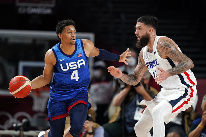 United States' Keldon Johnson (4) drives around France's Vincent Poirier during a men's basketball preliminary round game at the 2020 Summer Olympics, Sunday, July 25, 2021, in Saitama, Japan. (AP Photo/Charlie Neibergall)