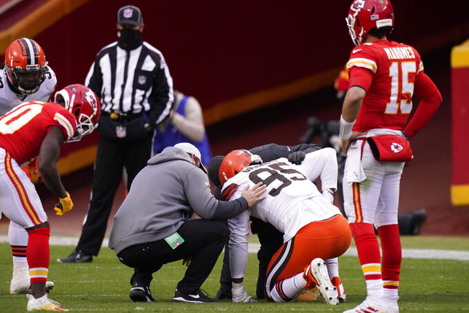 Cleveland Browns defensive end Myles Garrett (95) is helped off the field after getting injured during the second half of an NFL divisional round football game against the Kansas City Chiefs, Sunday, Jan. 17, 2021, in Kansas City. (AP Photo/Charlie Riedel)