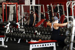 FILE - In this May 14, 2020, file photo, people work out at Metroflex Gym in Oceanside, Calif. California will allow schools, day camps, bars, gyms, campgrounds and professional sports to begin reopening with modifications starting Friday, June 12, 2020. (AP Photo/Gregory Bull, File)