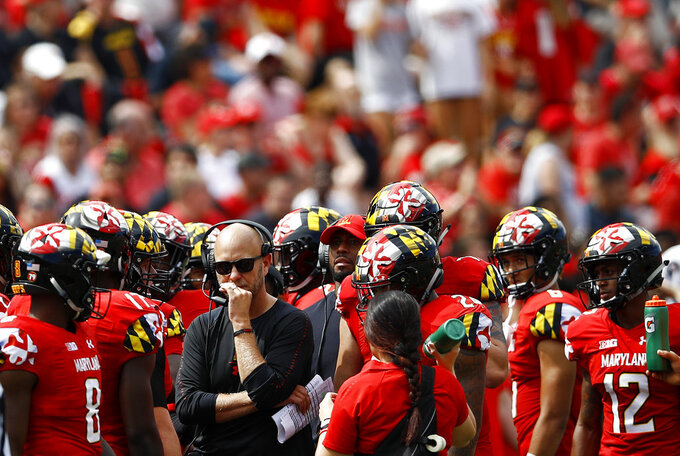 Maryland interim head coach Matt Canada, in black, gathers with players during a timeout in the first half of an NCAA college football game against Temple, Saturday, Sept. 15, 2018, in College Park, Md. (AP Photo/Patrick Semansky)