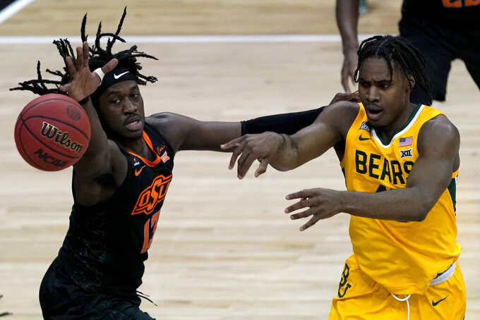 Baylor's Davion Mitchell, right, passes around Oklahoma State's Isaac Likekele (13) during the first half of an NCAA college basketball game in the semifinals of the Big 12 tournament in Kansas City, Mo., Friday, March 12, 2021. (AP Photo/Charlie Riedel)