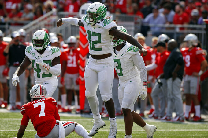 Oregon defensive end DJ Johnson, front, celebrates his sack of Ohio State quarterback C.J. Stroud on the final play of the game in the second half of an NCAA college football game Saturday, Sept. 11, 2021, in Columbus, Ohio. Oregon beat Ohio State 35-28. (AP Photo/Jay LaPrete)