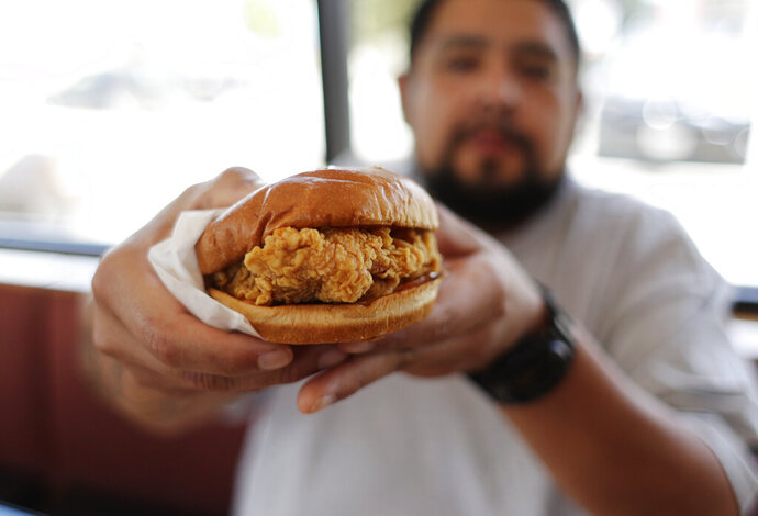 Randy Estrada holds up his chicken sandwiches at a Popeyes, Thursday, Aug. 22, 2019, in Kyle, Texas. After Popeyes added a crispy chicken sandwich to their fast-fast menu, the hierarchy of chicken sandwiches in America was rattled, and the supremacy of Chick-fil-A and others was threatened. It's been a trending topic on social media, fans have weighed in with YouTube analyses and memes, and some have reported long lines just to get a taste of the new sandwich. (AP Photo/Eric Gay)