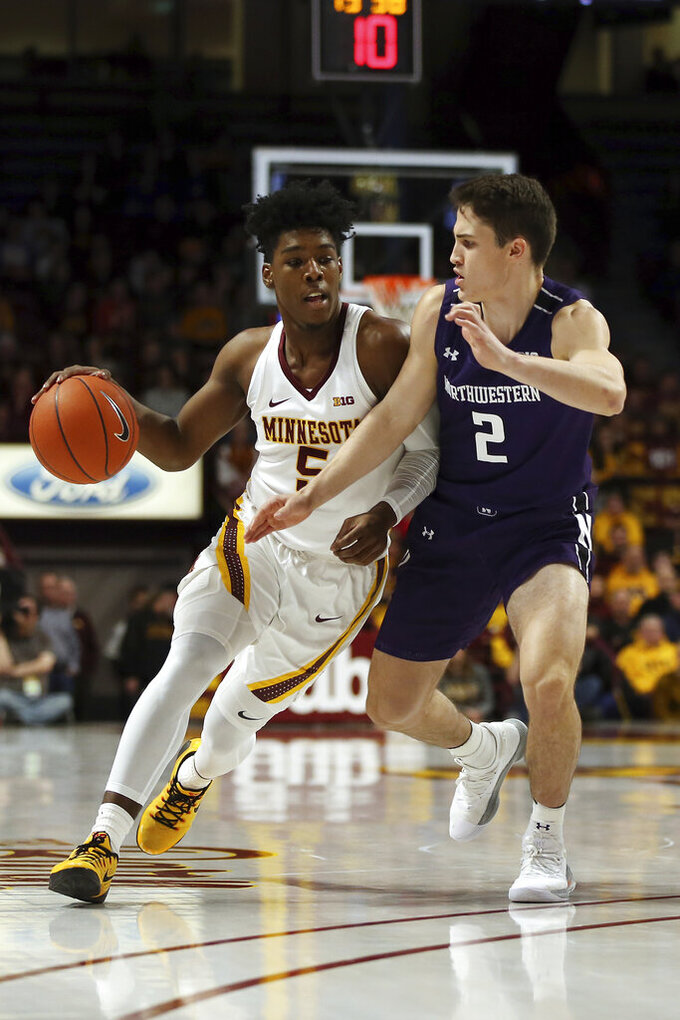 Minnesota's Marcus Carr, left, dribbles against Northwestern's Ryan Greer during an NCAA college basketball game Sunday, Jan. 5, 2020, in Minneapolis. (AP Photo/Stacy Bengs)