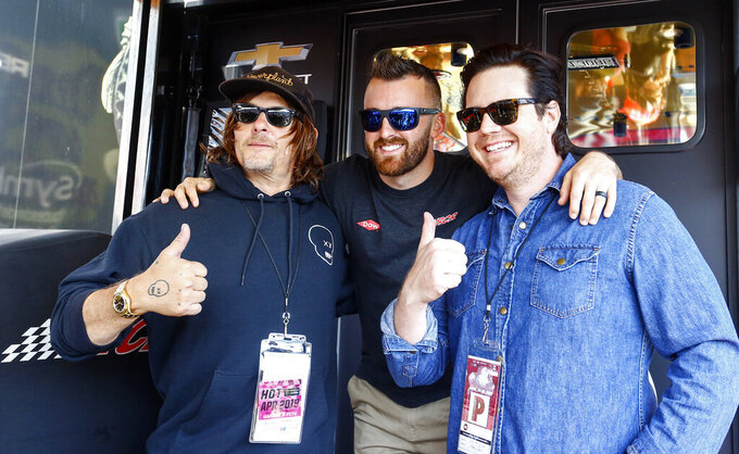 "Actors Norman Reedus, left, and Josh McDermitt, right, of ""The Walking Dead,"" pose with NASCAR Cup Series driver Austin Dillon, center, before the Geico 500 at Talladega Superspeedway, Sunday, April 28, 2019, in Talladega, Ala. (AP Photo/Butch Dill)"