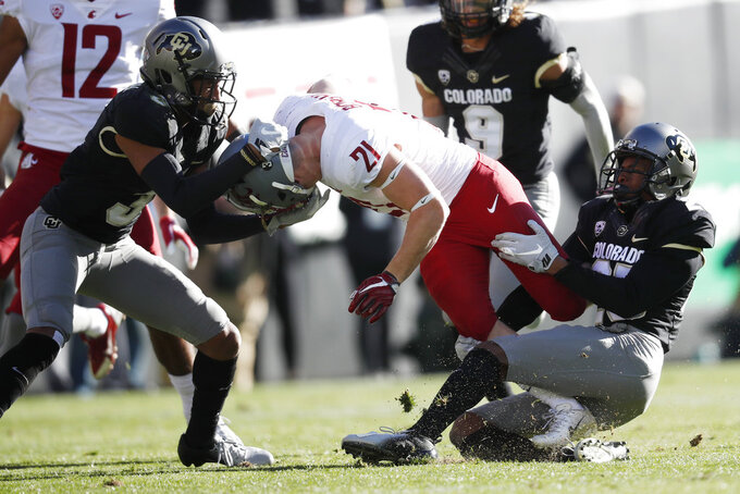 Washington State running back Max Borghi, center, is tackled by Colorado defensive back Derrion Rakestraw, left, and cornerback Mekhi Blackmon in the first half of an NCAA college football game Saturday, Nov. 10, 2018, in Boulder, Colo. (AP Photo/David Zalubowski)